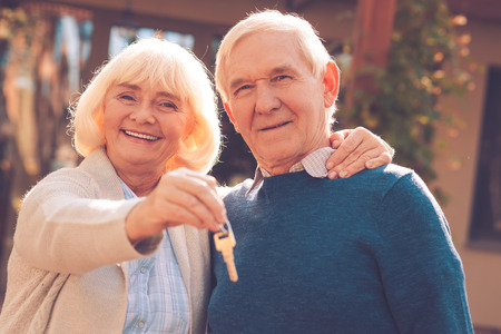 man outdoors: Happy senior couple. Happy senior couple bonding to each other and smiling while woman holding keys in her hand