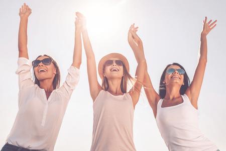 Godersi la vita. Basso angolo di vista di tre belle giovani donne si tengono per mano e alzando le braccia Archivio Fotografico - 47807277