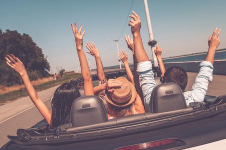 Genieten road trip. Achter mening van jonge gelukkige mensen genieten van road trip in hun converteerbare en het verhogen van hun armen omhoog