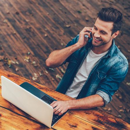 hombres jovenes: Trabajar en el aire fresco. Vista superior de un joven feliz trabajando en la computadora portátil y hablando por el móvil phonewhile sentado en la mesa de madera al aire libre