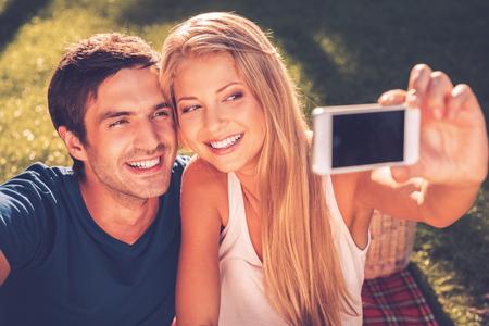 haciendo el amor: Nos encanta selfie! Feliz joven cariñosa pareja haciendo selfie y sonriendo mientras está sentado juntos en el césped en el parque