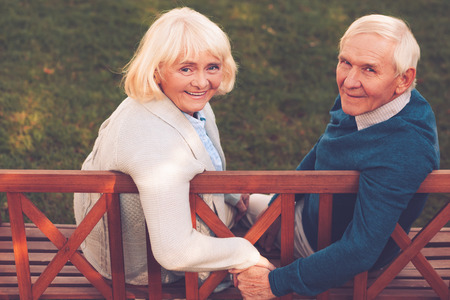 senior men: Happy to be together. Rear view of happy senior couple holding hands and looking at camera with smile while sitting on the park bench together Stock Photo
