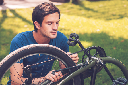 only adult: Repairing his bike. Confident young man fixing his bike while kneeling on grass
