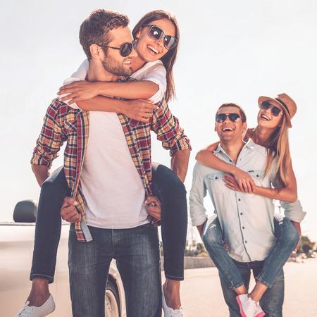 gafas de sol: Amigos que se divierten. Dos parejas jóvenes hermosas que se divierten cerca de su convertible blanco Foto de archivo