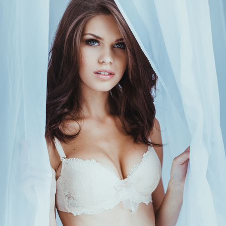 beauty breast: Beauty in lingerie. Beautiful young brown hair woman in lingerie looking out from the white tulle