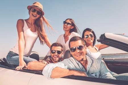 Passer du bon temps ensemble. Groupe de jeunes heureux, appréciant voyage sur la route dans leur cabriolet blanc et souriant à la caméra