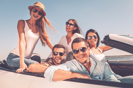 cool people: Spending great time together. Group of young happy people enjoying road trip in their white convertible and smiling at camera