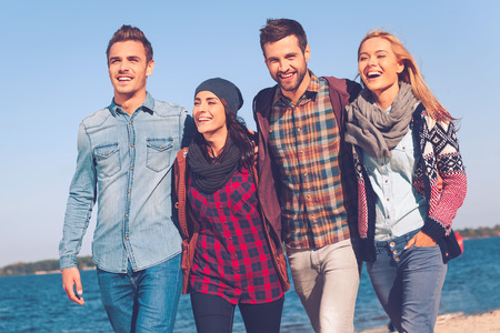carefree: Young and carefree. Four young happy people bonding to each other and smiling while walking by the beach together Stock Photo