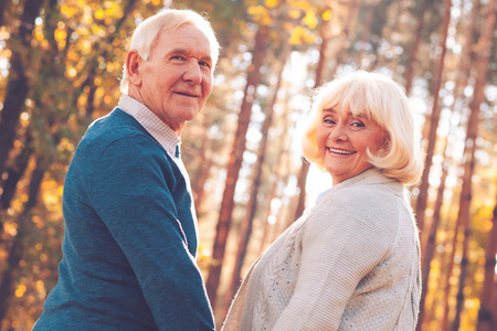 We love spending time together. Rear view of happy senior couple holding hands and looking over shoulder while walking by park together photo