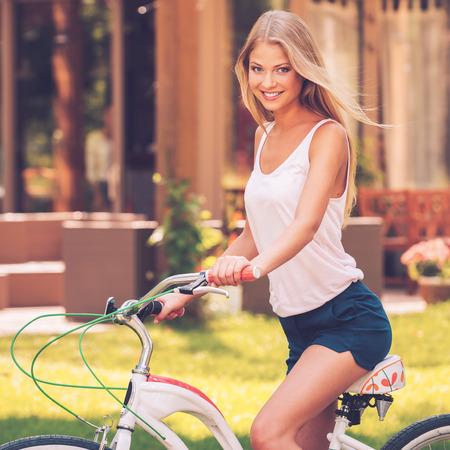 cabello rubio: Listo para montar. Vista lateral de la joven y bella mujer de pelo rubio sonriendo y mirando a usted mientras que monta su bicicleta al aire libre Foto de archivo