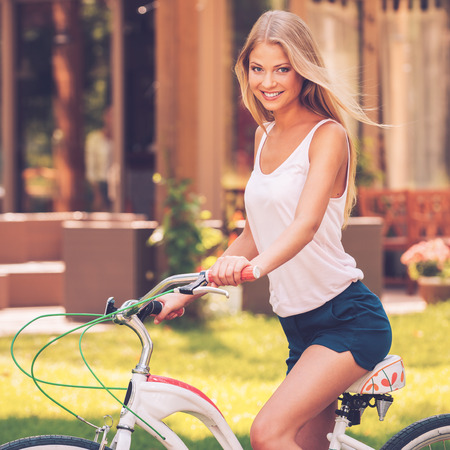 cheveux blonds: Ready to ride. Side view of beautiful young blond hair woman smiling and looking at you while riding her bicycle outdoors Banque d'images