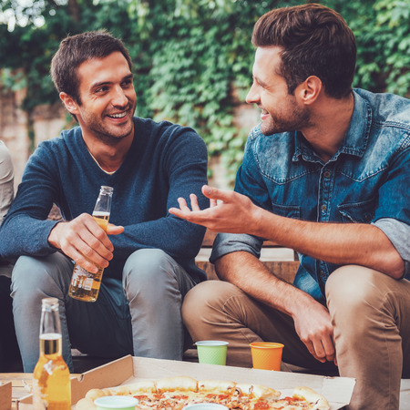 people relax: Friendly talk. Three happy young people drinking beer and talking to each other while sitting outdoors