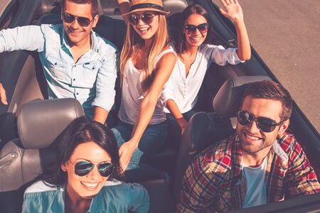 enjoyment: Fun travel. Top view of young happy people enjoying road trip in their white convertible and raising their arms