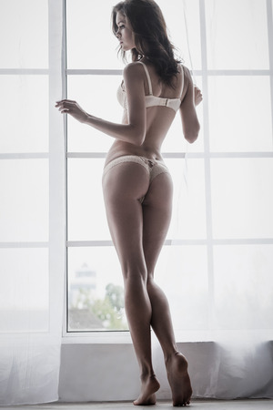 beautiful sex: Gorgeous beauty. Full length rear view of beautiful young woman in lingerie standing near the window