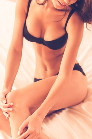 black breast: She got beautiful legs. Top view of beautiful young brown hair woman in black lingerie sitting in bed and touching her leg