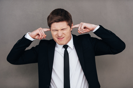 facial expression: This sound is too loud. Frustrated young man in formalwear closing his ears with fingers and making a face while standing against grey background Stock Photo