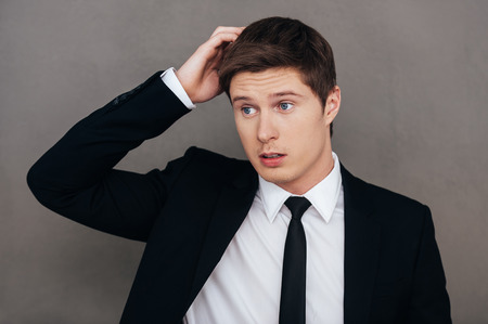 He is not sure about it. Frustrated young man in formalwear holding hand in hair and looking away while standing against grey background Stock Photo