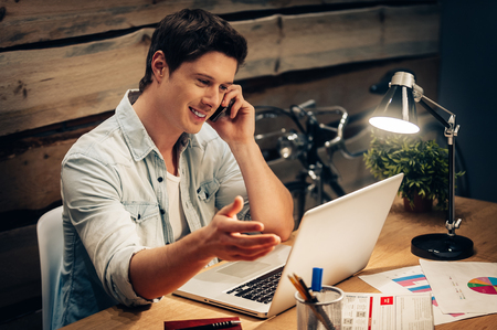 office lighting: Discussing new project. Cheerful young man talking on the mobile phone and looking at laptop while sitting at his working place