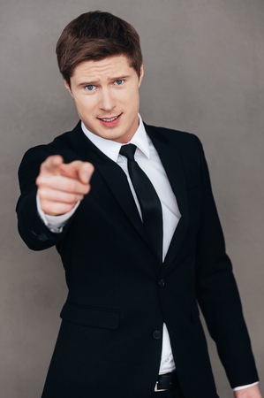 bossy: Do it right now! Bossy young man in formalwear pointing you while standing against grey background