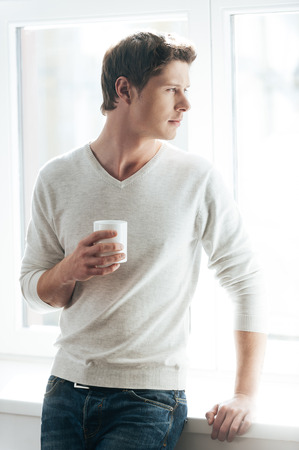 hombre tomando cafe: Enjoying good morning. Cheerful young man drinking coffee and looking at camera while standing against window Foto de archivo