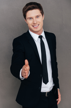 shaking out: Welcome on board! Cheerful young man in formalwear stretching out hand for shaking while standing against grey background
