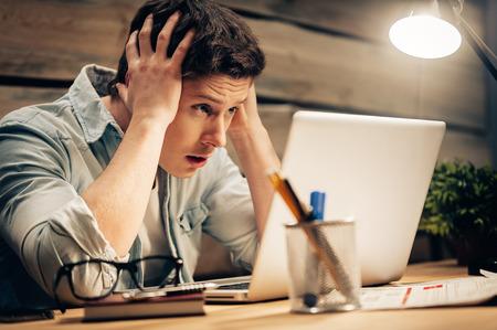 reflexionando: Sentirse enfermo y cansado. joven frustrado cabeza en las manos y mirando a la computadora port�til mientras trabajar hasta tarde en su lugar de trabajo