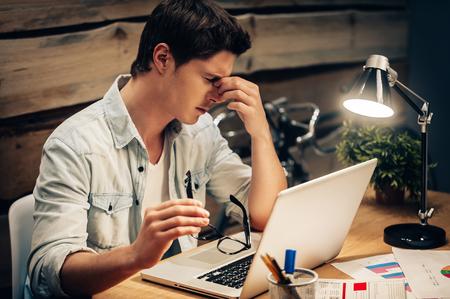 yeux: Se sentir épuisé. Frustré jeune homme en gardant les yeux fermés et l'air fatigué tout en travaillant tard dans son lieu de travail Banque d'images
