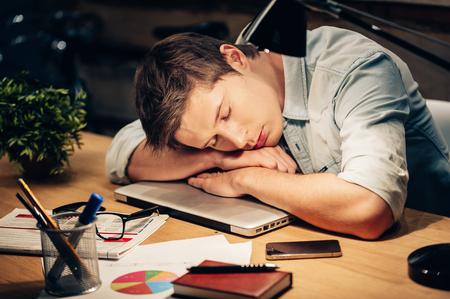 あまりにも多くの作業。若い男が彼の職場でノート パソコンで彼の頭をもたれながら寝て