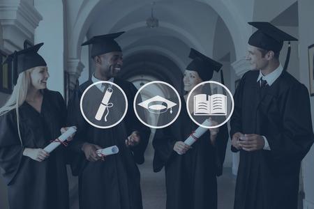 personas de pie: Listo para un futuro brillante. Cuatro graduados universitarios en vestidos de graduaci�n caminando por pasillo de la universidad y hablar