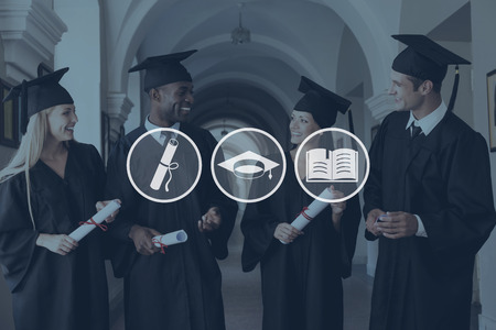 people standing: Ready to bright future. Four college graduates in graduation gowns walking along university corridor and talking Stock Photo