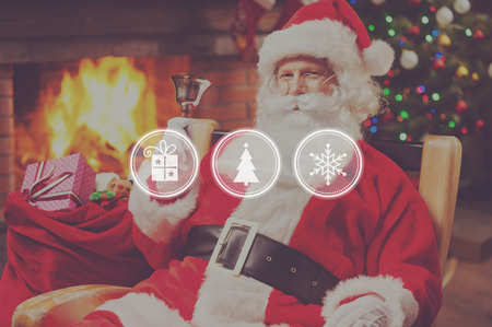 Christmas is coming! Cheerful Santa Claus sitting at his chair and ringing a bell with fireplace and Christmas Tree in the background