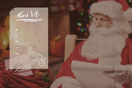 Wish list. Traditional Santa Claus looking at his sack with presents and holding a paper while sitting at his chair with fireplace and Christmas Tree in the background