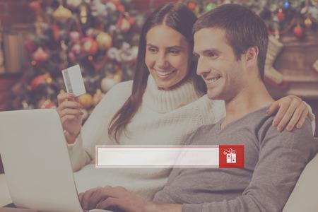 mujer alegre: Encuentra regalos en línea. Hermosa joven pareja de comprar en línea durante el uso de ordenador junto con el árbol de Navidad en el fondo
