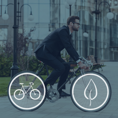 businessman in office: Green ride. Side view of young businessman looking forward while riding on his bicycle Stock Photo