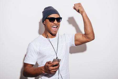 young adult men: I love this track! Happy young African man in headphones holding his music player and gesturing while standing against white background