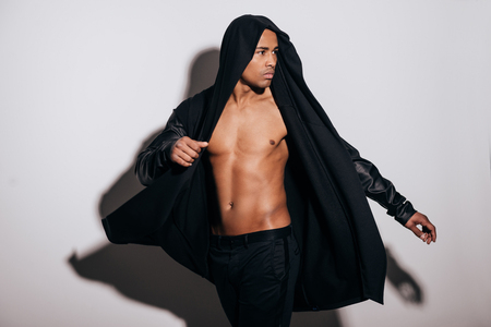 hooded shirt: Style in motion. Handsome young African man in hooded shirt looking over shoulder while standing against white background