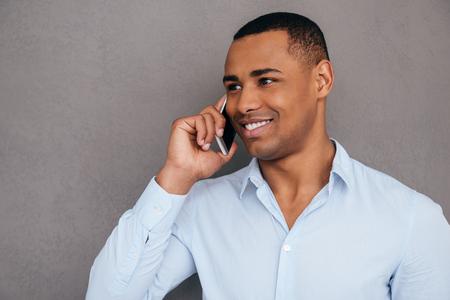 hombres guapos: Buena charla. joven africano confianza hablando por tel�fono m�vil y sonriendo mientras est� de pie contra el fondo gris