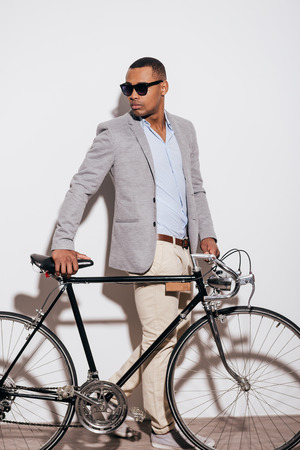 retro styled: My bike is my style. Full length of confident young African man standing near his retro styled bicycle and against white background Stock Photo