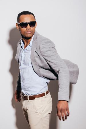 hombres guapos: Fresco y de moda. joven africano conf�a en gafas de sol que desgastan la chaqueta y mirando por encima del hombro mientras est� de pie contra el fondo blanco