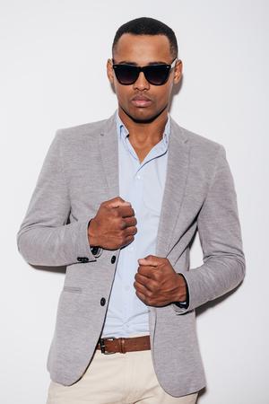 mannequin africain: Trendy beau. Confiant jeune homme africain dans des lunettes de soleil ajustant sa veste et en regardant la caméra tout en se tenant sur le fond blanc