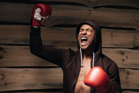 fully unbuttoned: Used to win. Happy young African man in hooded shirt and boxing gloves raising his arms and keeping eyes closed while standing against wooden background