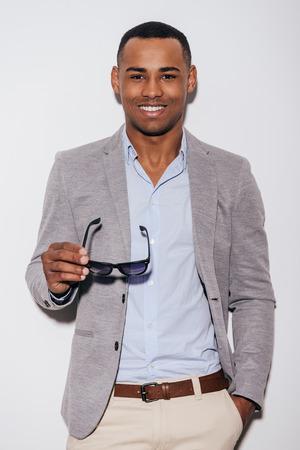 uomini belli: Esprimendo il suo buon umore. Fiducioso giovane africana che porta gli occhiali da sole e sorridente, mentre in piedi contro sfondo bianco