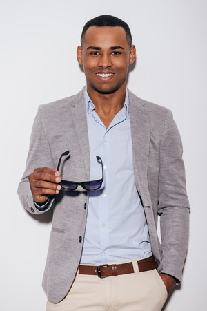 only one man: Expressing his good mood. Confident young African man carrying his sunglasses and smiling while standing against white background Stock Photo