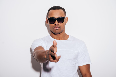 male models: Hands up! Serious young African man in sunglasses gesturing finger gun while stretching out hand and standing against white background