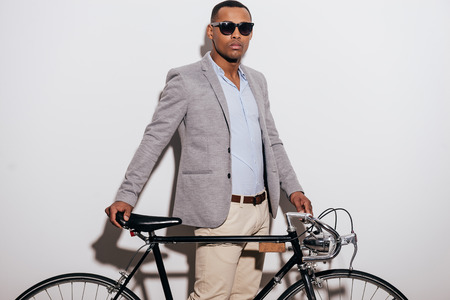 leaning: My bike is my lifestyle. Confident young African man in sunglasses leaning at his retro styled bicycle and looking at camera while standing against white background