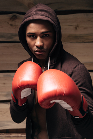 fully unbuttoned: I am ready to fight. Confident young African man in hooded shirt and boxing gloves looking at camera while standing against wooden background