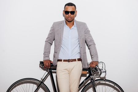 retro styled: Me and my bike. Confident young African man in sunglasses leaning at his retro styled bicycle and looking at camera while standing against white background