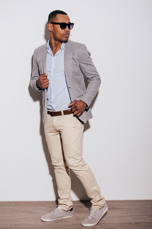 looking over shoulder: He got trendy look. Confident young African man in smart casual clothing looking over shoulder while standing against white background