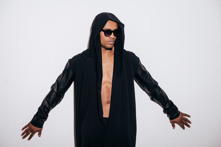 modelos negras: Confiado y con estilo. El hombre africano joven de moda en la camisa de pie contra el fondo blanco con capucha Foto de archivo
