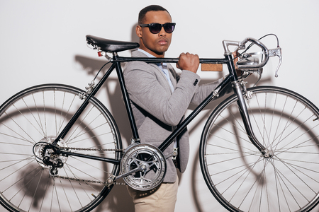 retro styled: In his own style. Confident young African man in sunglasses carrying his retro styled bicycle on shoulder and looking at camera while standing against white background